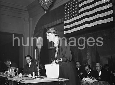 Woman speaking into a microphone at a patriotic event, American flag in background,  ca. 1934