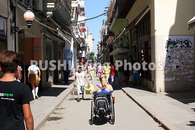 Woman using a wheelchair strolling down a Cuban street