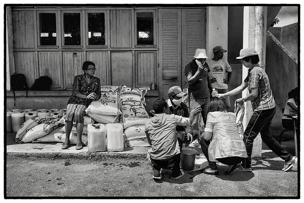 Residents line up at a primary school in Antananarivo to buy rice and oil at a low price offered by the local authorities, on...