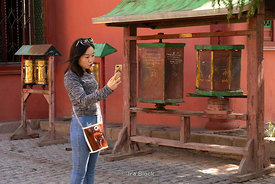 A woman taking a selfie at Gandantegchinlen Monastery, Monglia's largest functioning Buddhist monastery in Ulaanbaatar.  The ...