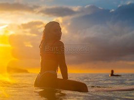 Girl on surfboard at sunset