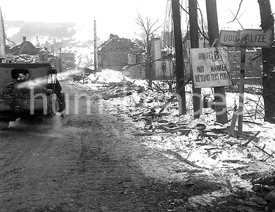 Original caption: An American jeep enters the shell-torn town of Houffalize, Belgium, by the main road. The town was retaken ...