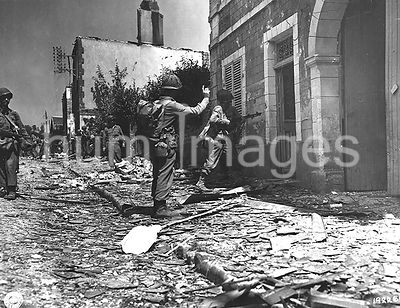Original caption: As two infantrymen station themselves near the door, a BAR gunner enters a building in Percy, France, suspe...