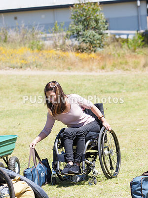 Woman using a wheelchair carrying equipment to a camp ground