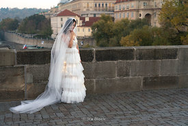 A bride poses for a photoshoot on Charles Bridge in Prague, Czech Republic