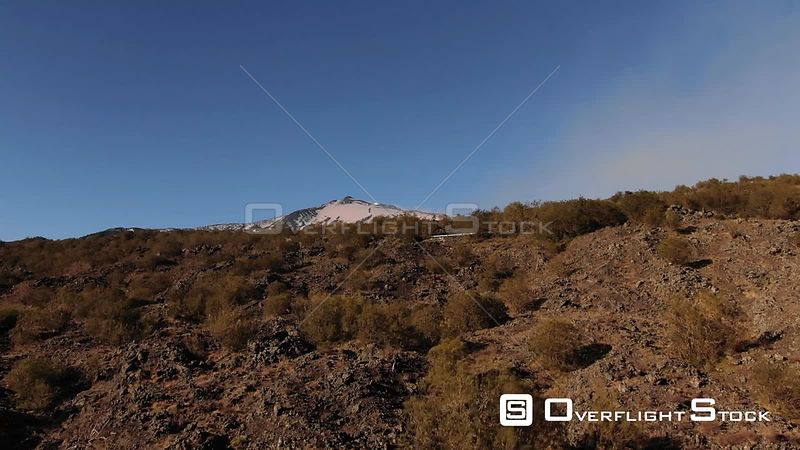 Aerial view over lava rock and shrubs the summit of mount Etna in Sicily Italy