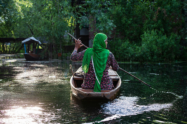 Woman Paddling Down Canal Leading to Floating Market