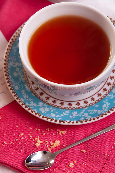 A delicious cup of black tea ona a pink placemat