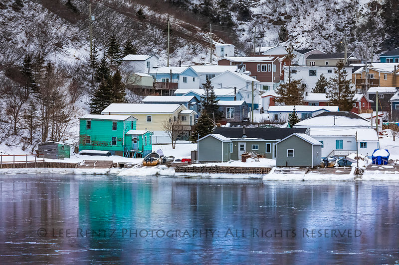 Waterfront with glaze of sea ice at the outport of Grey River, which is snuggled along a fjord, viewed from the ferry Marine ...
