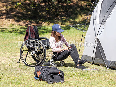 Woman using a wheelchair pitching a tent