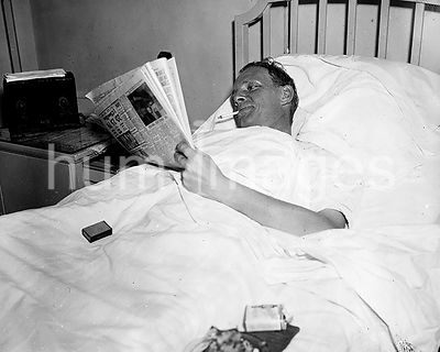 Man in hospital bed smoking a cigarette while reading a newspaper ca. 1936