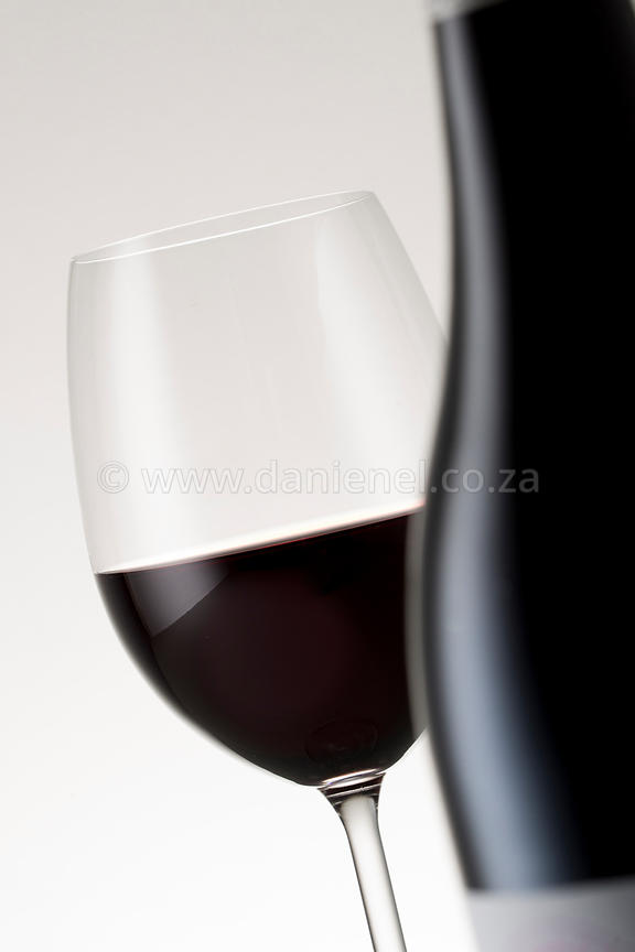 A glass of red wine with a bottle in the foreground