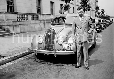 Senator Huey P. Long standing by an automobile ca. 1935
