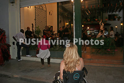 Woman using a wheelchair outside a Cuban nightclub