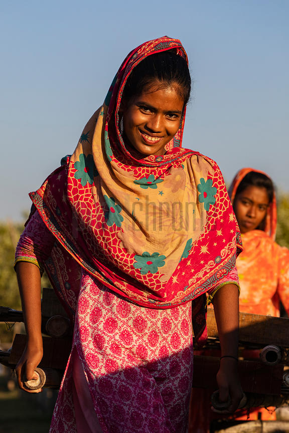 Portrait of a Young Woman Carrying Racks of Dried Fish for Evening Storage