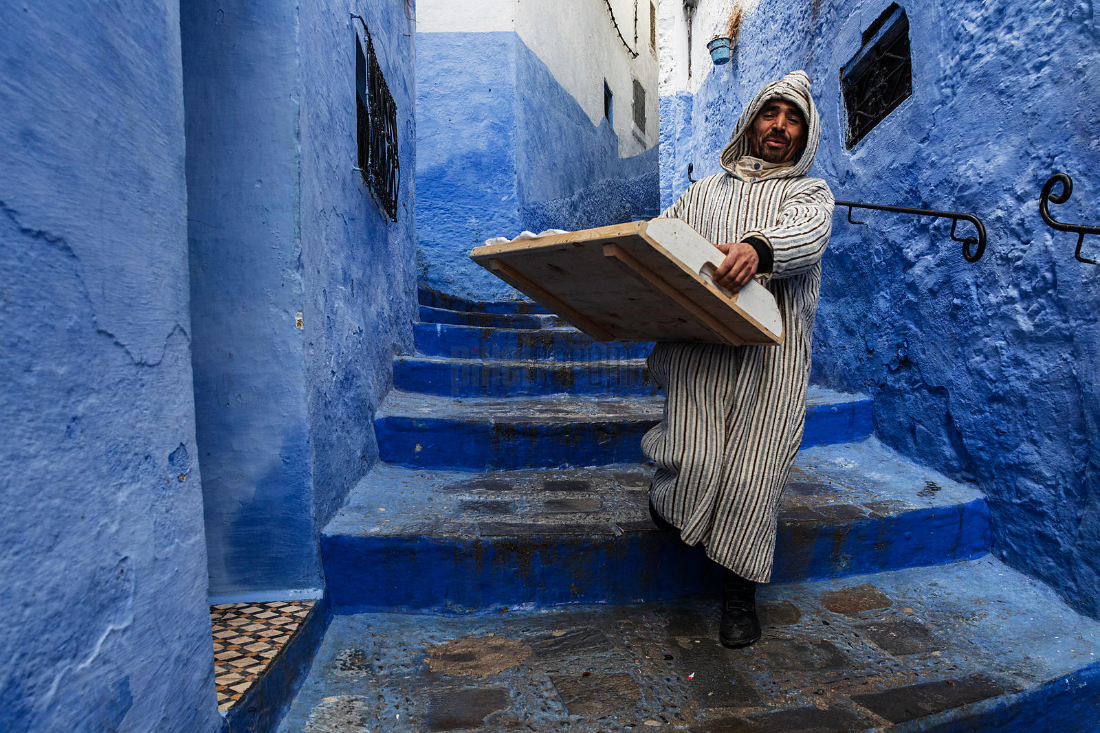 A Man Carries Fresh Baked Goods in a Street in Chefchaouen