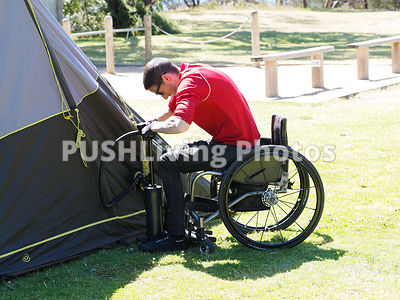 Man using a wheelchair pitching a tent