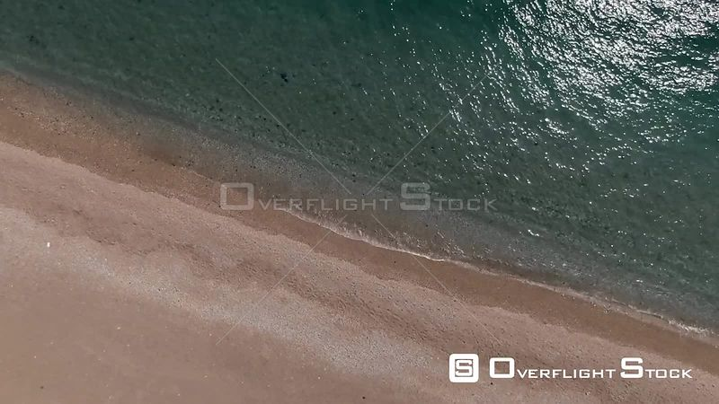 Aerial Descending Turning View of the Sea and a Sandy Beach With Sun Reflections