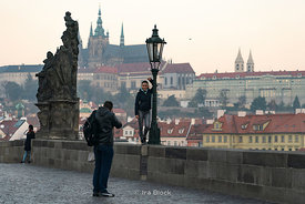 A woman gets photographed on Charles Bridge in Prague, Czech Republic