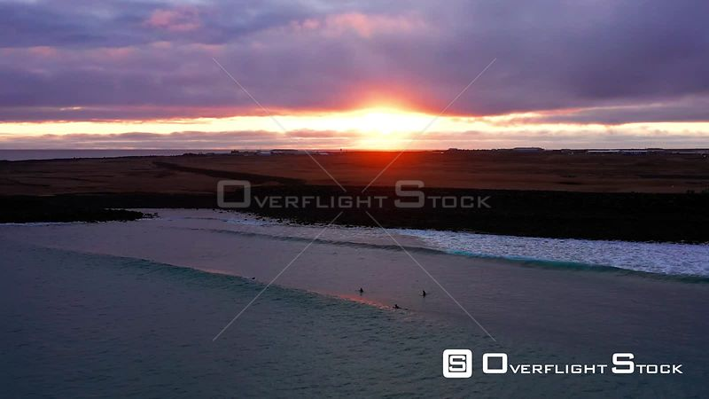 A Glide Over Surfers at Sunset in Iceland.