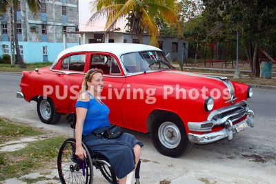 Woman using a wheelchair in a Cuban street with a classic car
