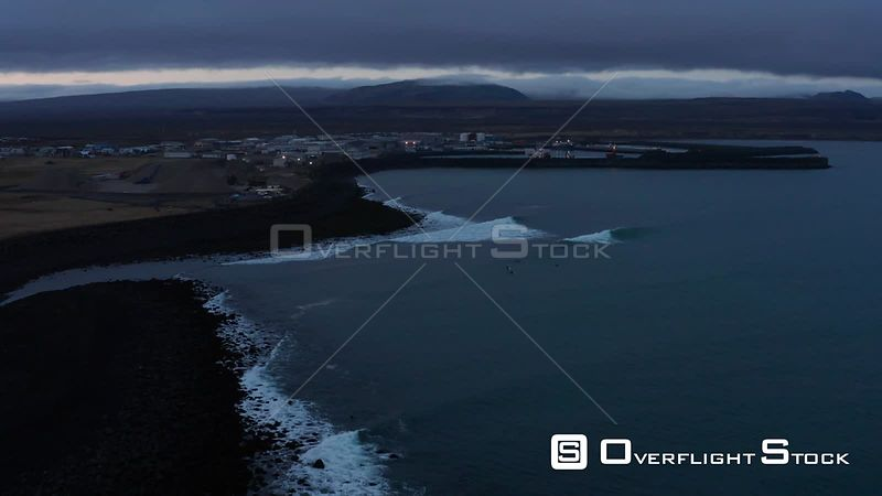 Waves and Surfers in Twilight With a Small Harbour Behind in Iceland.