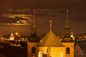 A view of the moon over the city of Prague as seen from the Old Town Bridge Tower  in Prague, Czech Republic