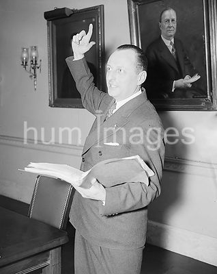 Man speaking while holding a book ca. 1935