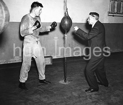 A trainer working with a boxer in a gym ca. 1936