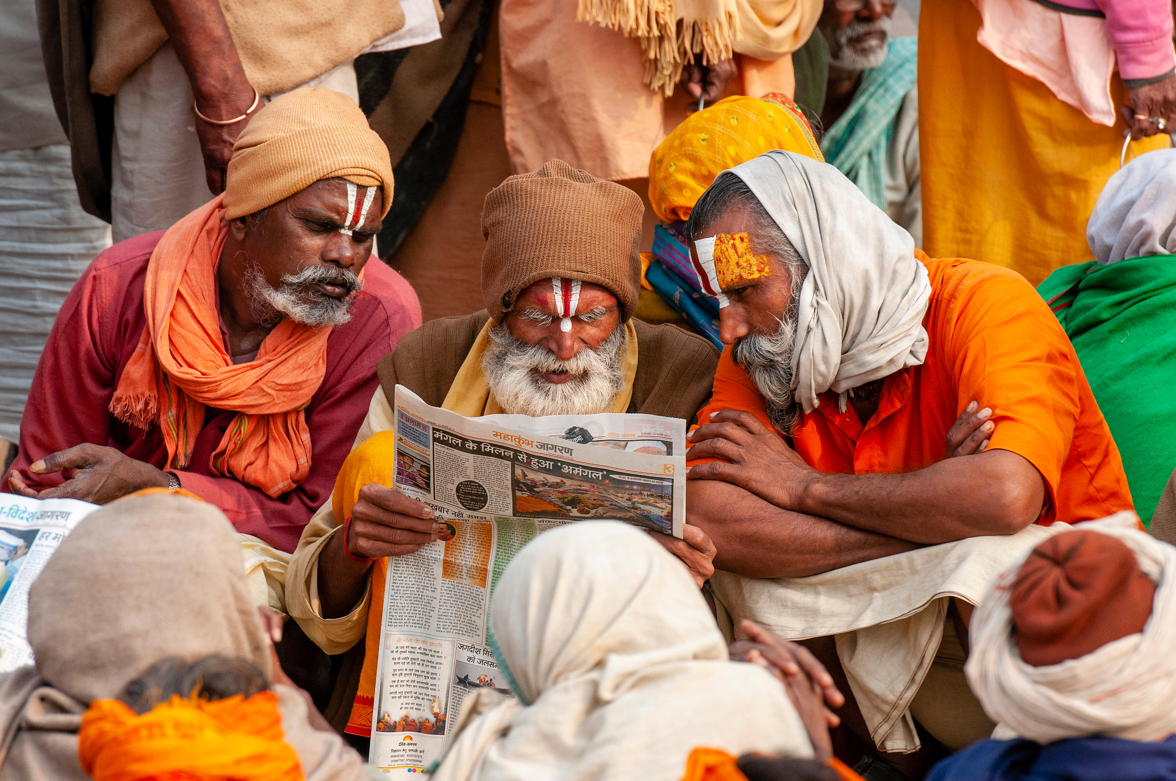 A group of pilgrims read newspaper while the others wait for langar (communal meals) during the kumbh mela, Allahabad