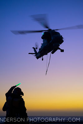 Green means go. The Flight Deck Officer signals the helicopter to land..A SH-2G(I) Seasprite practices attaching and detachin...