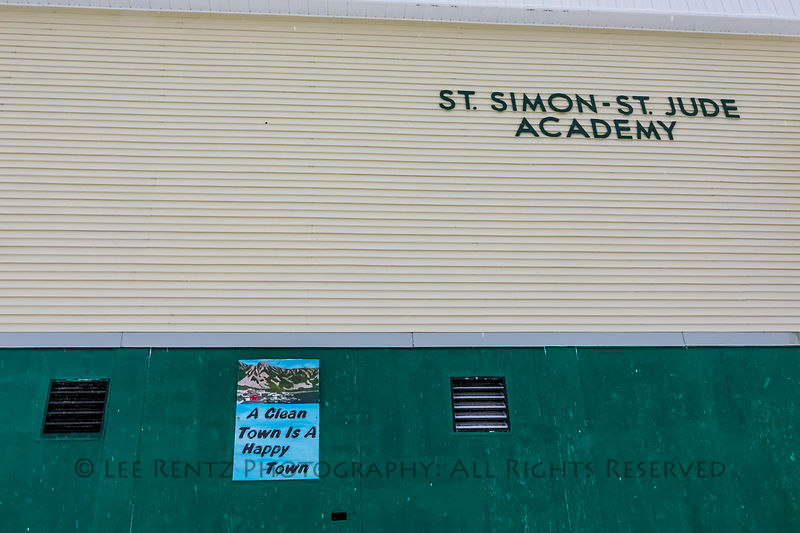 "Sign on St. Simon-St. Jude Academy, the public school, saying ""A Clean Town is a Happy Town,"" in Francois"