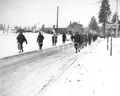 Members of the 101st Airborne Division move out of Bastogne, Belgium, to drive the Germans who have besieged them for ten da...