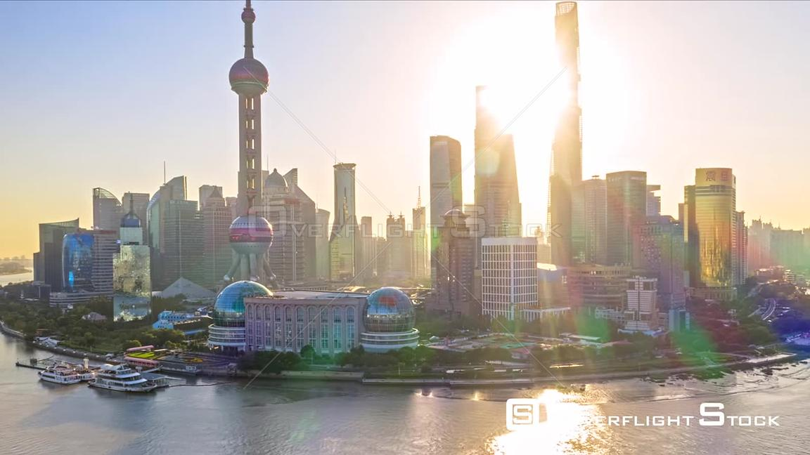 China Shanghai Aerial Hyperlapse flying around landmark waterfront, financial center, with sunlight glare