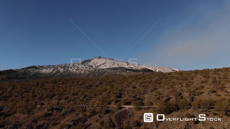 Aerial view over ofthe summit of mount Etna in Sicily Italy with lava rock and shrubs in the foreground