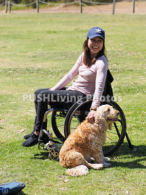 Woman using a wheelchair patting a dog