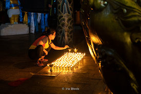 A woman lighting candles inside the Gandantegchinlen Monastery, a Tibetan-style monastery in Ulaan Baatar, Mongolian.