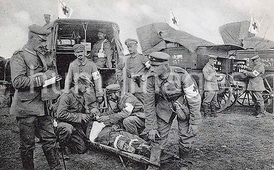 ON THE BATTLEFIELD. German Medical Officers giving wine to a severely wounded soldier ca. 1918