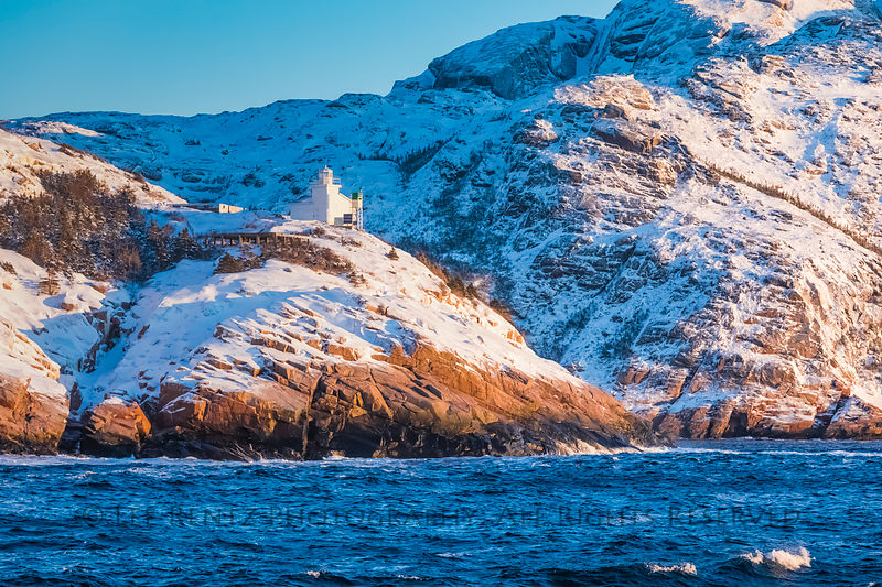 West Point Light Tower at mouth of Francois Bay, viewed in winter morning light from the ferry Marine Voyager in Newfoundland