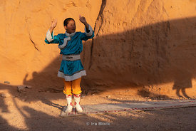 A mongol kid dancing to Mongolian music instruments at the Flaming Cliffs, Bayanzag, in the south Gobi desert, Mongolia.
