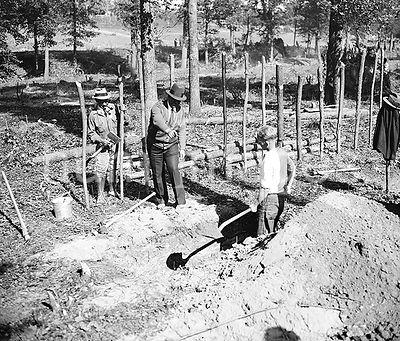 """A"" boss is shown here instructing a transient worker in ditch digging at ""Tugwelltown,"" a.k.a. Greenbelt, Maryland ca. Octo..."