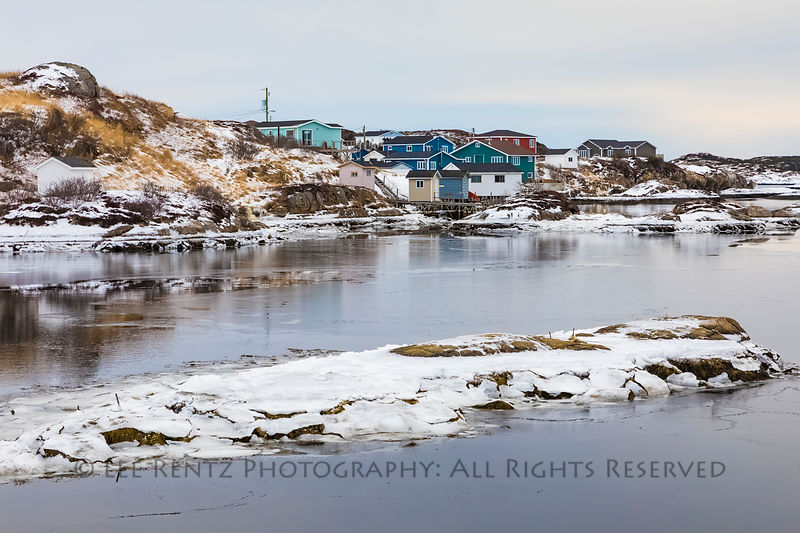 View of colorful houses across rocky bay from Sandbanks Provincial Park in Burgeo, Newfoundland