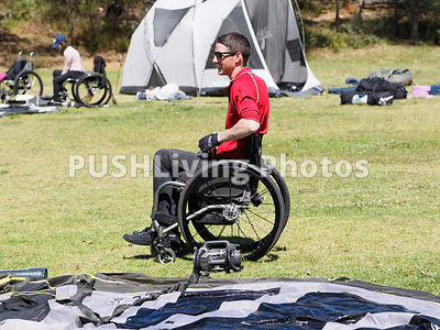 Woamn using a wheelchair pitching a tent