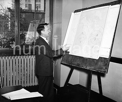 Man looking at a map on a board ca. 1934