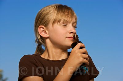 Girl smelling a generic brown medicine style bottle.