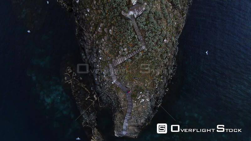 Aerial top down view of faraglione grande, a basalt volcanic formation on the sea by the East coast of Sicily. Italy
