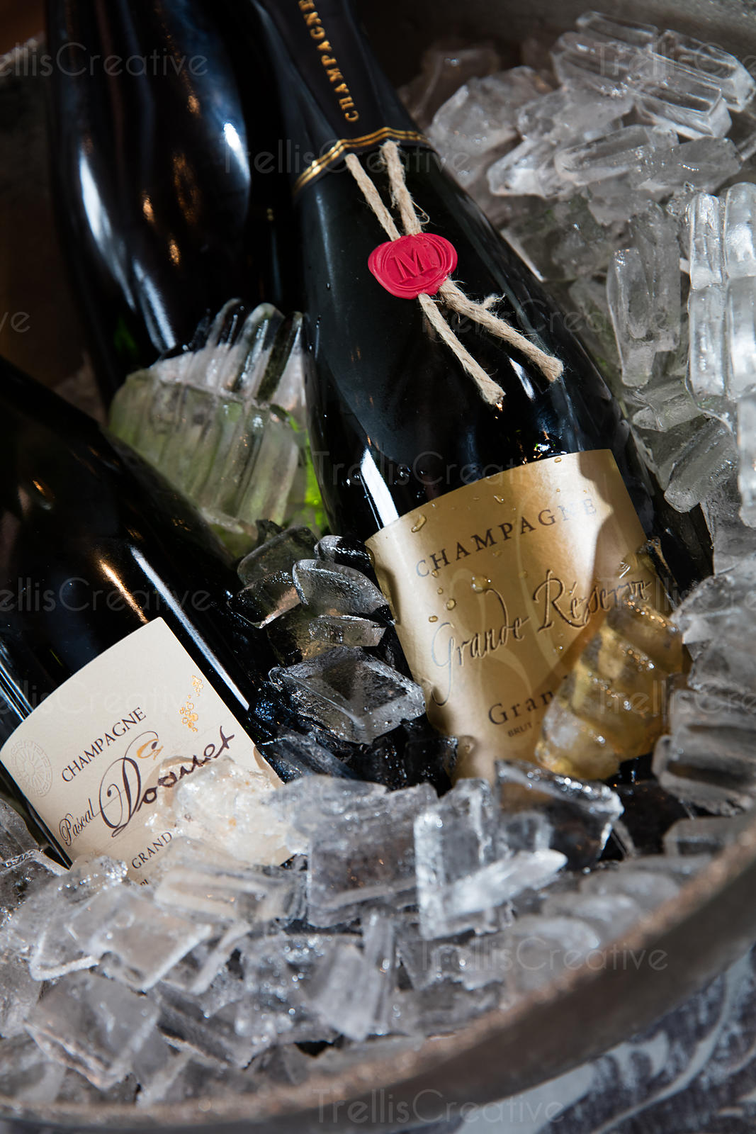 Close up of three bottles of champagne on ice.