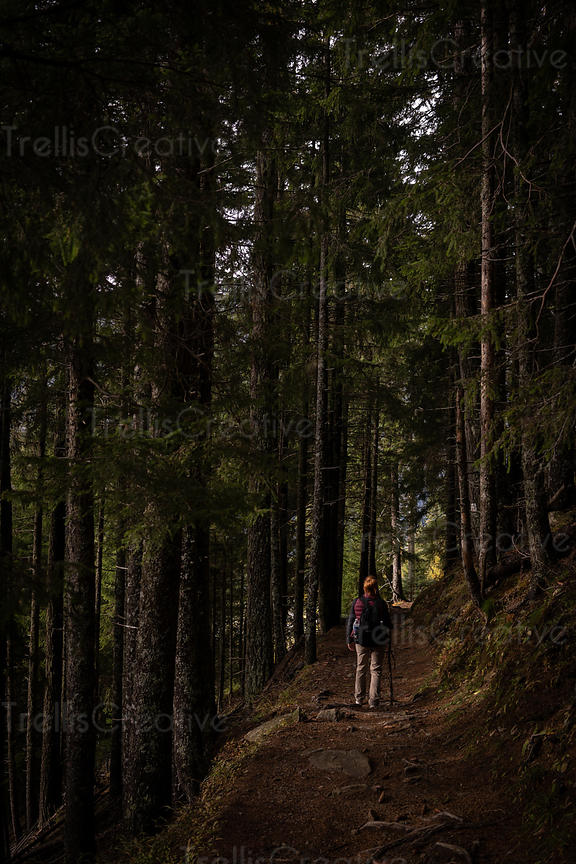 A young redheaded woman hiking alone in the deep dark forest
