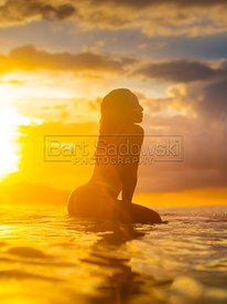 Woman sitting on surfboard at sunset