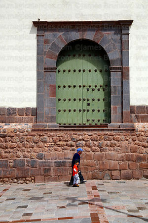 Old man and boy walking past Inca wall and Santa Ana church door, Cusco, Peru